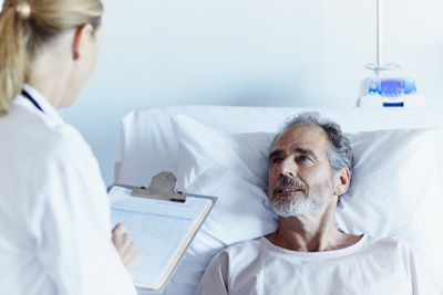 Man in a hospital bed looking at a doctor who's taking notes