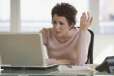 A woman is frustrated looking at her latop