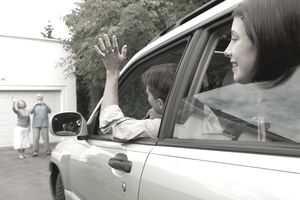 Teen and friends waving at grand parents from inside a vehicle as they back it out of the driveway.