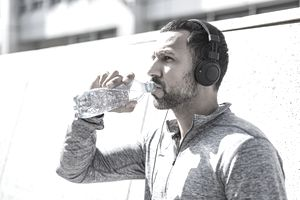 A man in a sweatsuit takes a break from exercising wearing headphones and drinking water from clear plastic bottle.