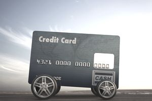 Car made out of credit card driving on remote road