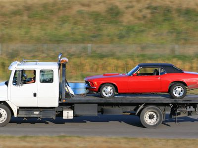 Red two-door sports car on the back of a tow-truck