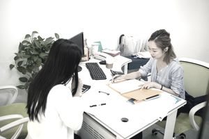Young Woman Sitting With Financial Adviser And Taking a Loan