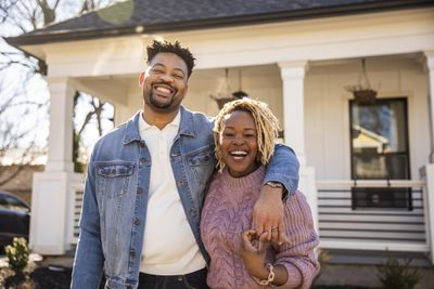 happy couple in front of a home