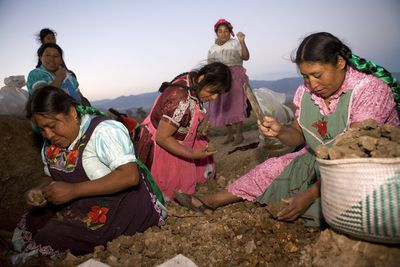 Mexican women breaking apart clay for making pottery