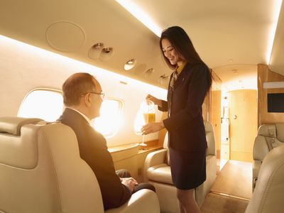 An execuitve flys in a private jet while a stewardess serves him a drink