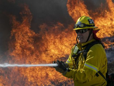 A firefighter with a hose, fire raging behind him