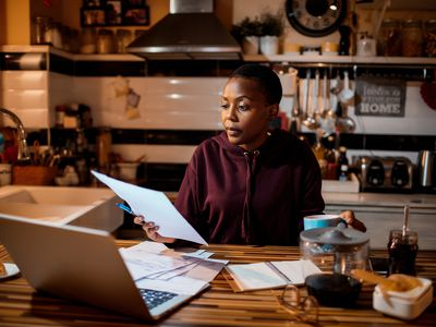 A woman reviews her investments at home in the evening.