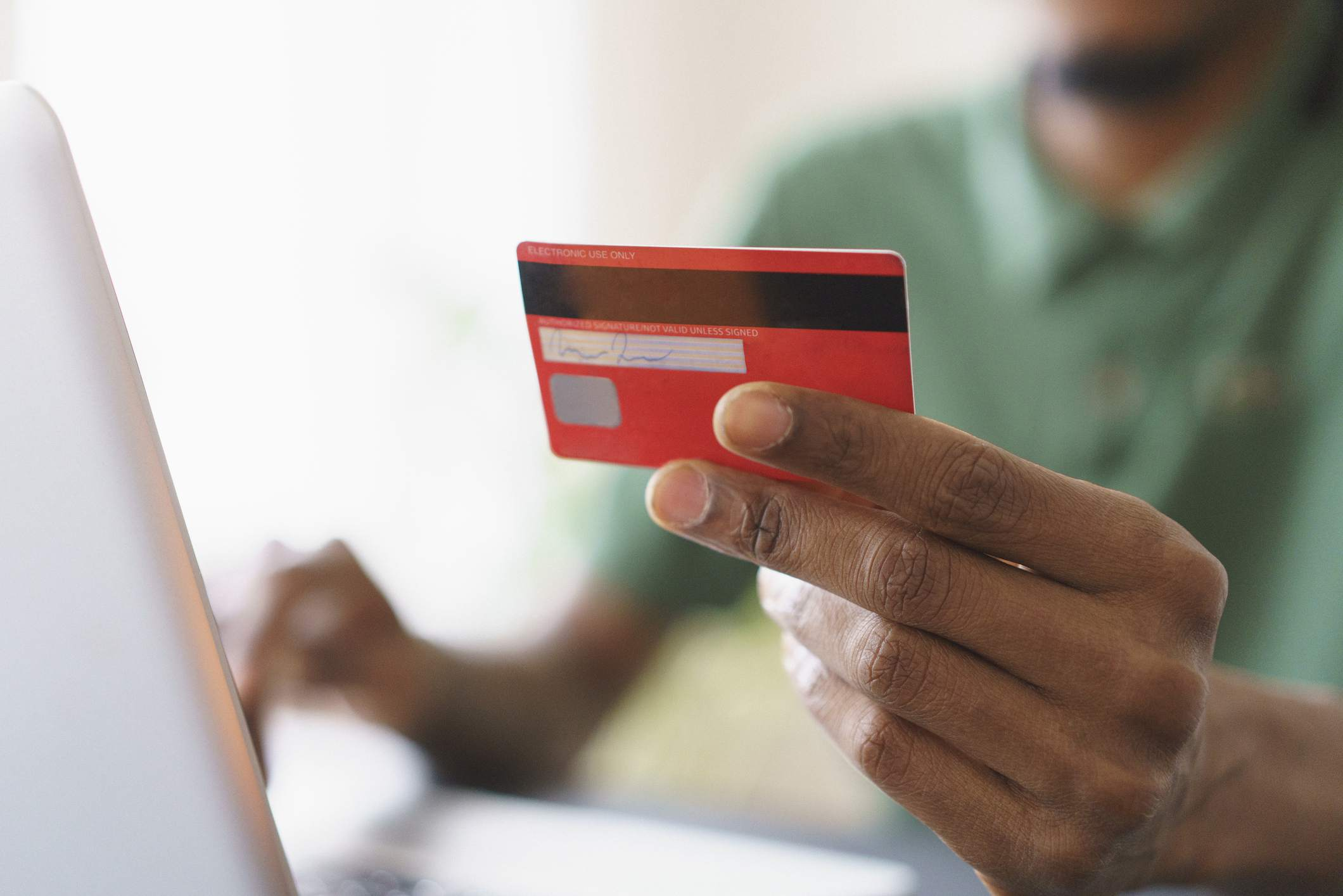 Close-up of man's hand holding a credit card in front of a laptop