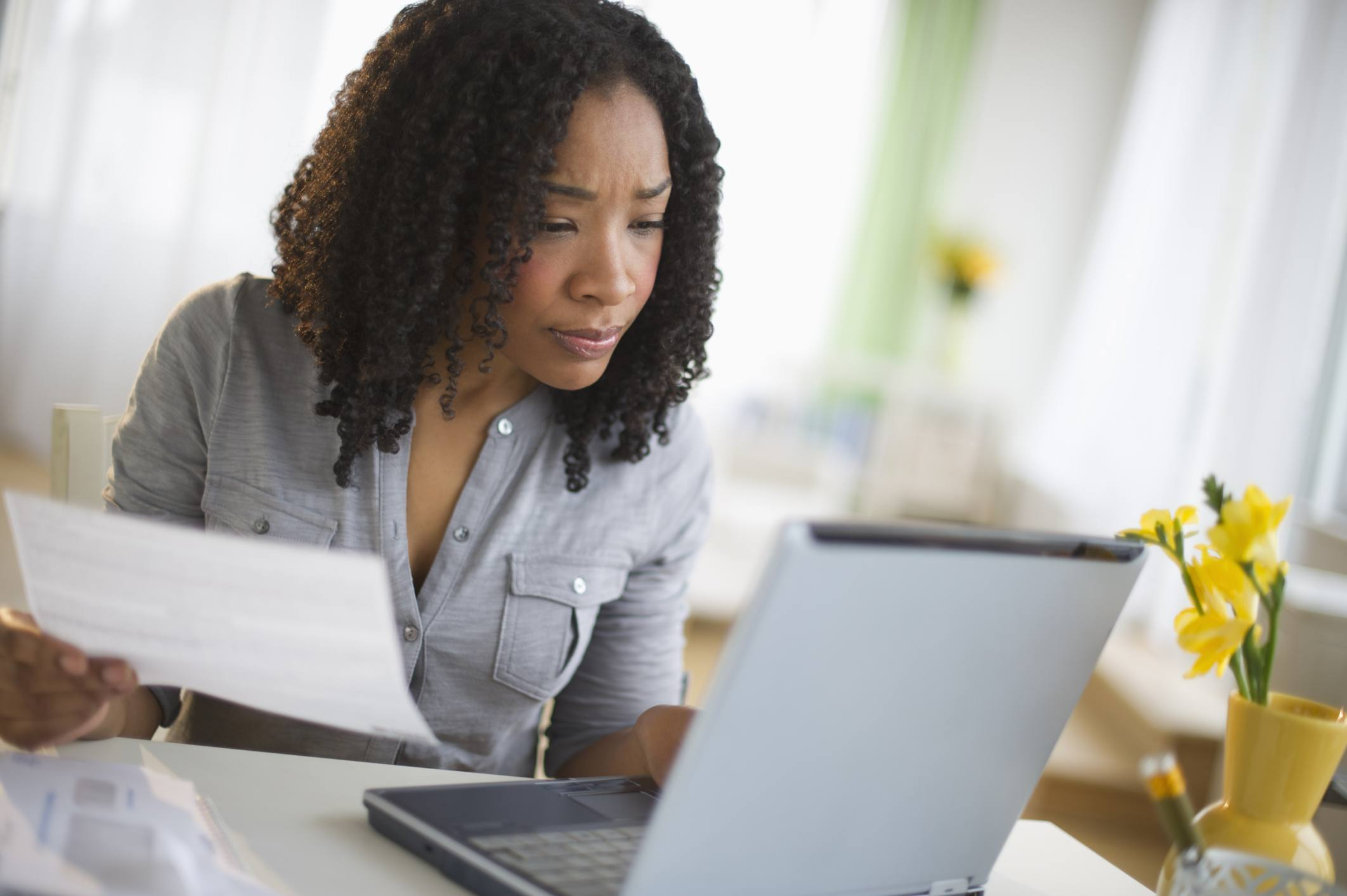 Woman paying credit card bills online to build good credit