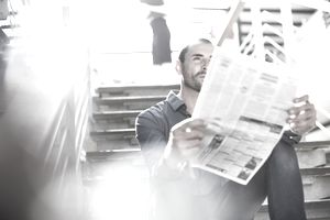 Man reading the newspaper while sitting on stairs.