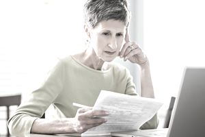 Woman appearing stressed looking at papers and laptop