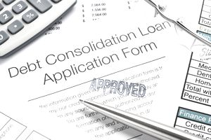 an approved debt consolidation loan application lays under a calculator, pen, and eyeglasses