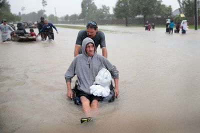 Man pushing another man in a wheelchair through the floodwaters of Hurricane Harvey