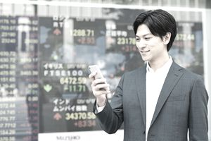 Young businessman checking his phone in front of stock prices