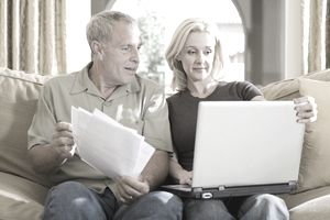 Couple sitting on couch looking at documents together