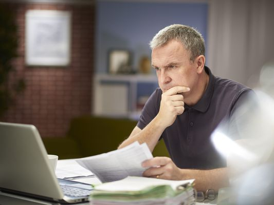 Worried man reading through a stack of bills after a call from a debt collector.