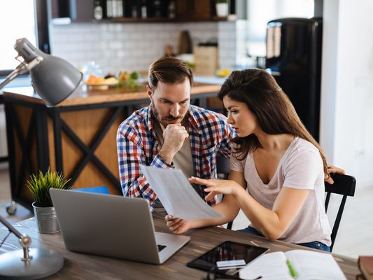 A worried young couple reviews their monthly bills and consider their mortgage relief program options.