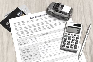 Car insurance application form with toy car, calculator and pen