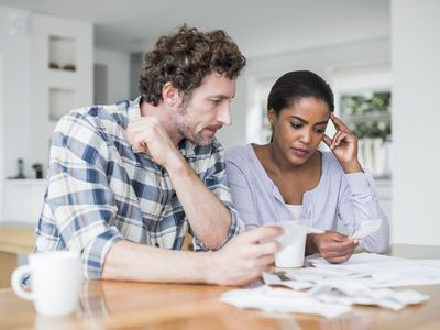Tense couple reading bills together