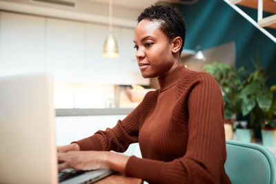 person at computer in brown sweater
