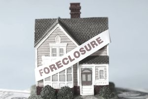 Foreclosure sign on house figurine