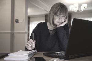A woman at home sorting her home finances online