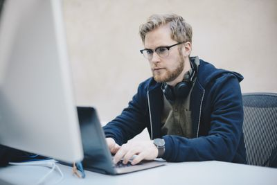 Young adult in hoodie looking intently at laptop screen