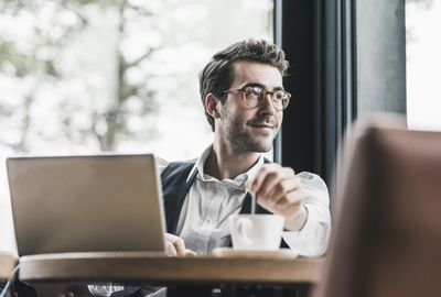 Investor ponders his tech mutual funds at a PC over a cup of coffee.