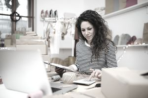 Young entrepreneur/business owner at home processing orders