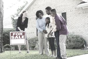 Family with a real estate agent outside home for sale