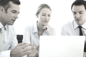 business professionals looking at a computer in a meeting