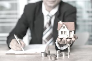 real estate and property concept - close up of hands holding house or home model