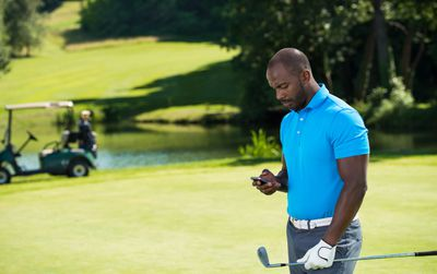 Golfer on sunny course holds club and looks at smartphone