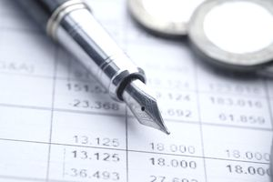 Pen and coins on balance sheet