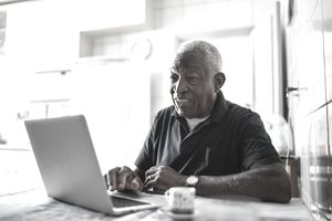 Gray-haired man at a laptop in his kitchen.
