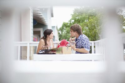 young married couple arguing about finances at a table on the balcony