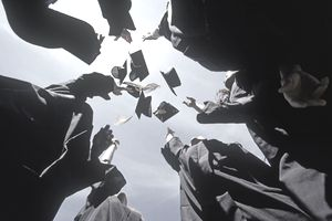 College graduates in a circle tossing their mortarboard caps into the air
