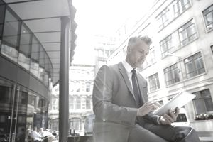 Silver-haired man in suit on tablet in city environment