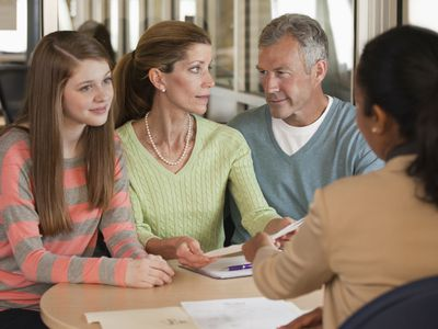 Parents and their child talking to a financial adviser about setting up a checking account