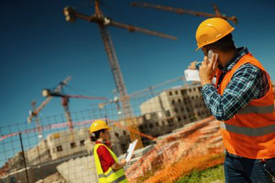 Municipal construction worker speaks on smartphone at job site