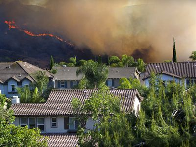 Homes near wildfire burning in hills