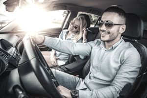 A man drives a car with a woman in the passenger seat. Both wear sunglasses and big smiles, as sun shines in through the passenger side window.