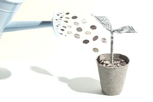 Origami dollar seedling being watered with coins