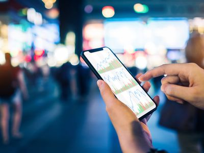 A stock trading app user reviews charts and balances with a mobile app in a crowded shopping and dining district.