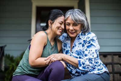 A young woman and her grey-haired mother hug and laugh while sitting on a porch