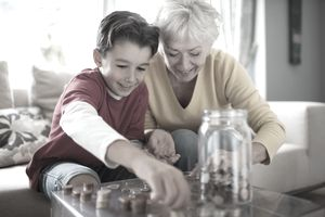 Grandmother and grandchild adding up change at a living room table