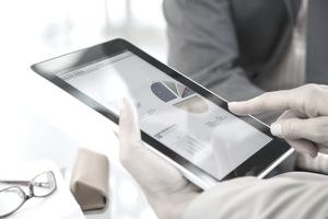 Business person reviewing financial data on digital tablet