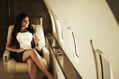 Woman with glass of champagne on private jet