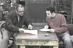 Manager and worker reviewing paperwork in factory